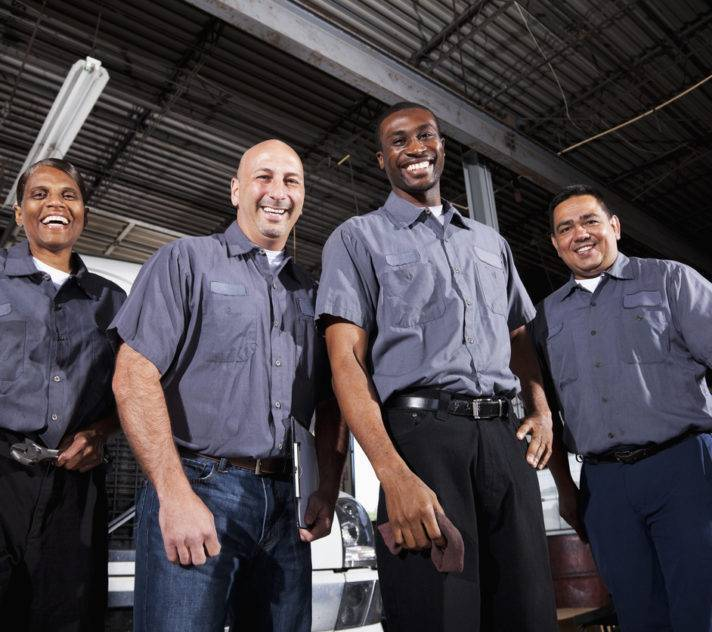 Multi-ehnic workers in service garage at trucking company.